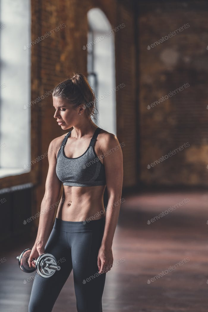 Athletic girl with dumbbells at workout