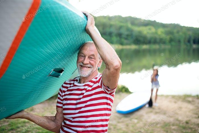 Senior man carrying paddleboard by lake in summer, looking at camera