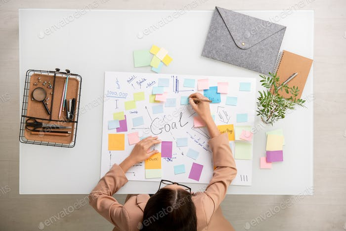 Overview of brunette businesswoman making working notes on sticky notepapers