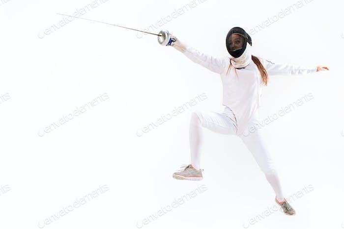 Mann mit Fechten Anzug üben mit Schwert gegen grau
