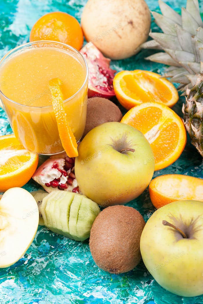 Close up of healthy and fresh fruits next to glass with detox ju