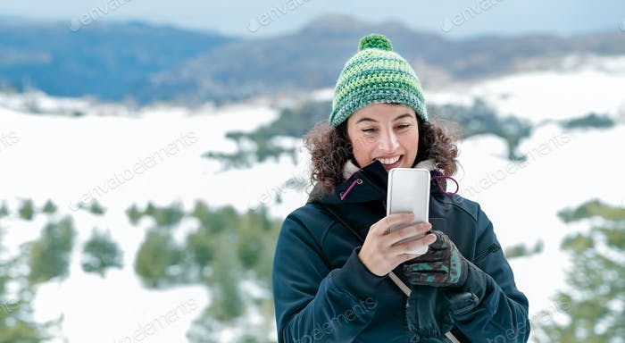 Happy woman using phone in the mountains