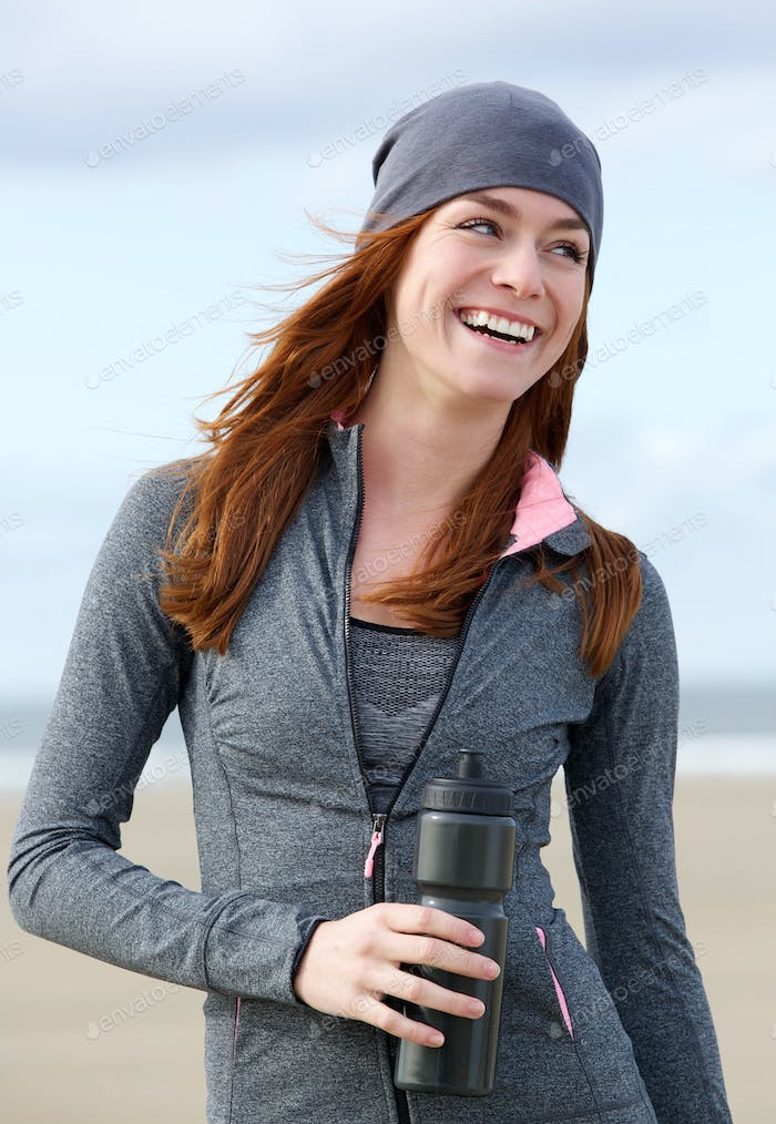 Smiling sporty woman standing outdoors with water bottle