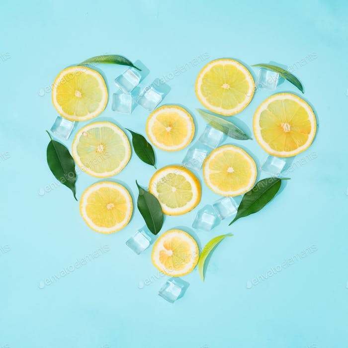 Creative summer background composition with lemon slices, straw and ice cubes.