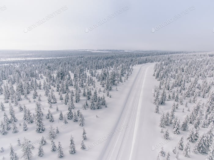 Aerial view of the road in the winter snow forest in Finland