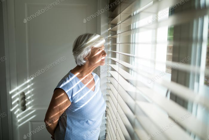 Senior woman looking through window in bedroom