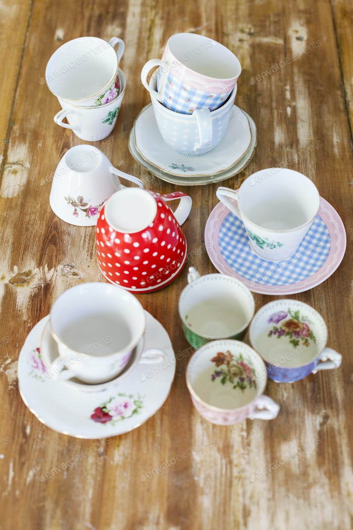 Various tea cups and saucers on wooden table