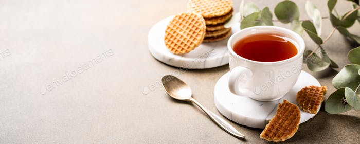 Cup of tea with syrupwaffles cookies