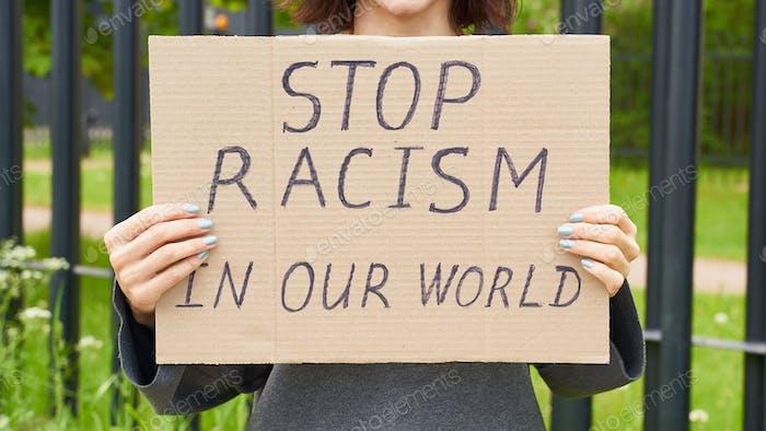 Detener el concepto de racismo. Persona blanca irreconocible sostiene signo con texto contra racista.