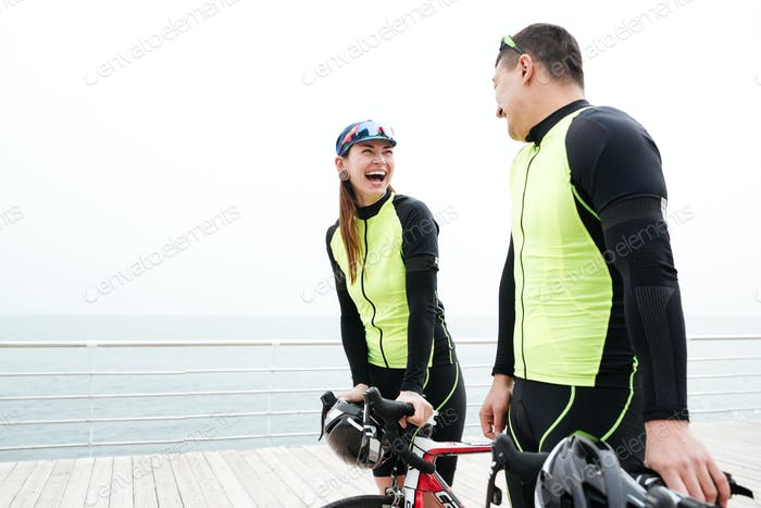 Couple with bikes talking and laughing on pier