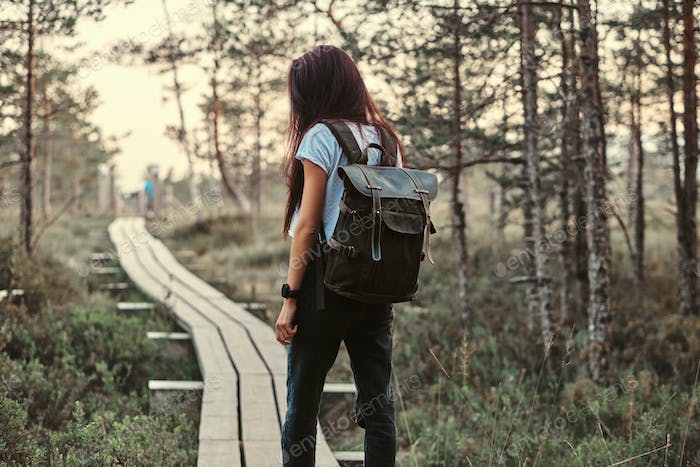 Tourist girl standing on a wooden footpath in beautiful forest.