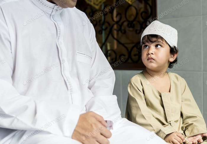 Muslim boy learning how to Salah