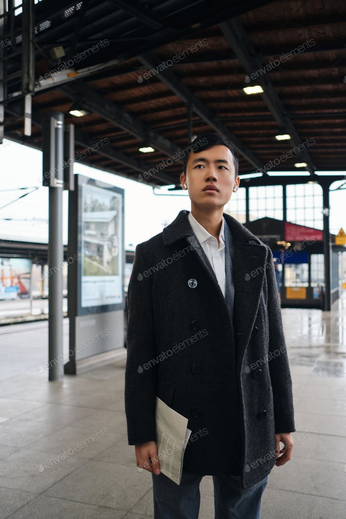 Young stylish Asian businessman in coat confidently waiting subway train
