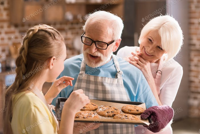 Happy grandfather, grandmother and grandchild looking at tray with delicious cookies