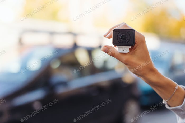 Video camera in a female hand, in the background the street