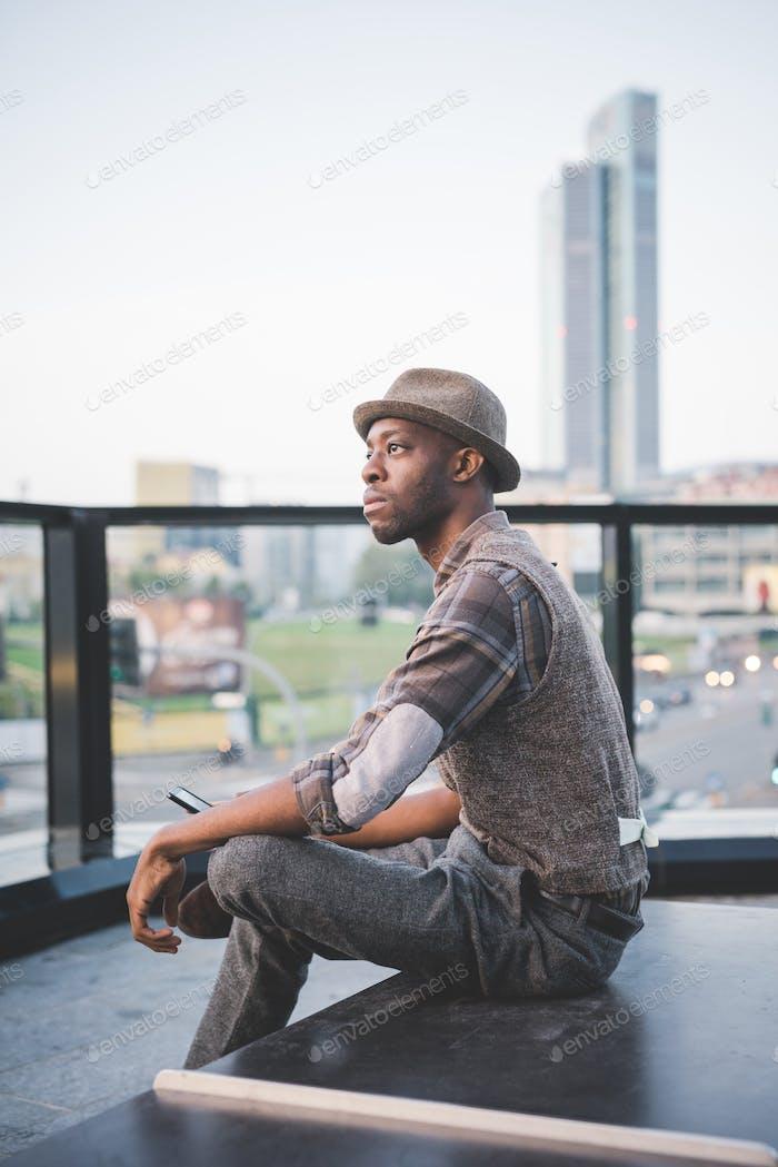 junge gutaussehende afro schwarz mann sitzend mit smartphone handheld,