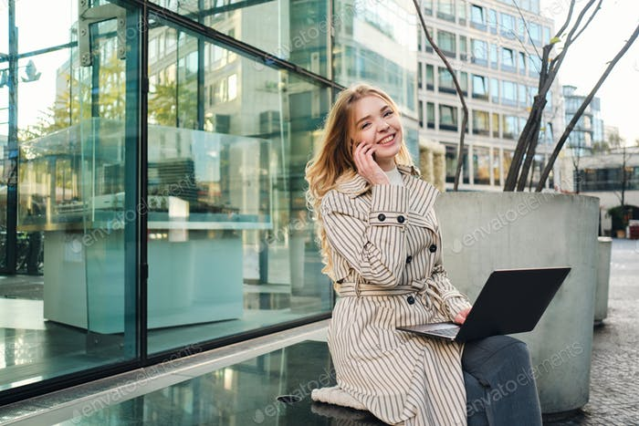 Young stylish businesswoman with laptop happily talking on cellphone working on street
