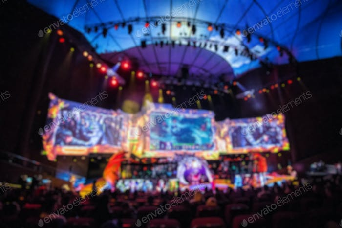 Blurred background of esports event at big arena with a lot of lights and screens