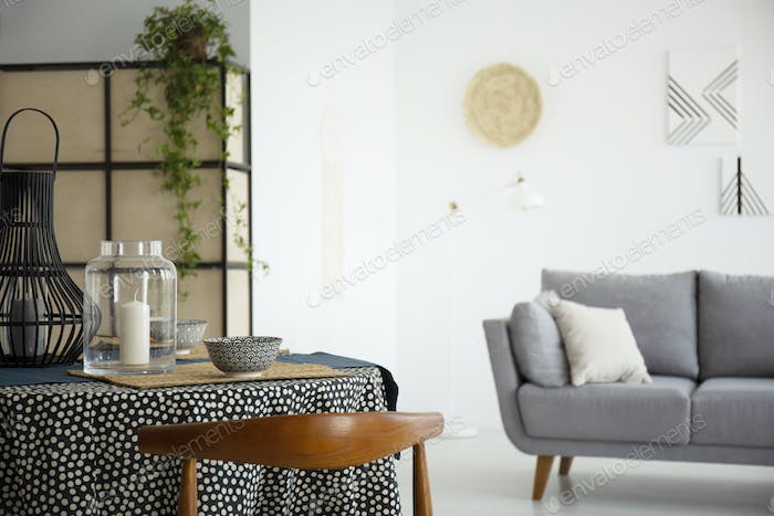 Candle on table in white living room interior with grey sofa and