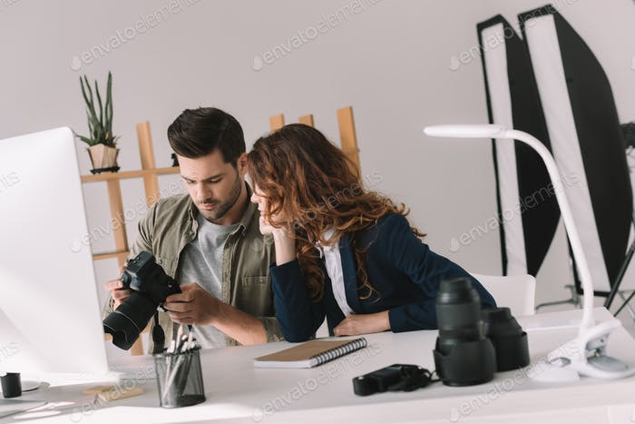 male photographer and model choosing photos for portfolio in modern office