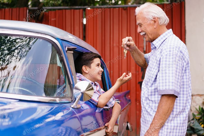 Senior Man Grandfather Giving Car Keys To Boy