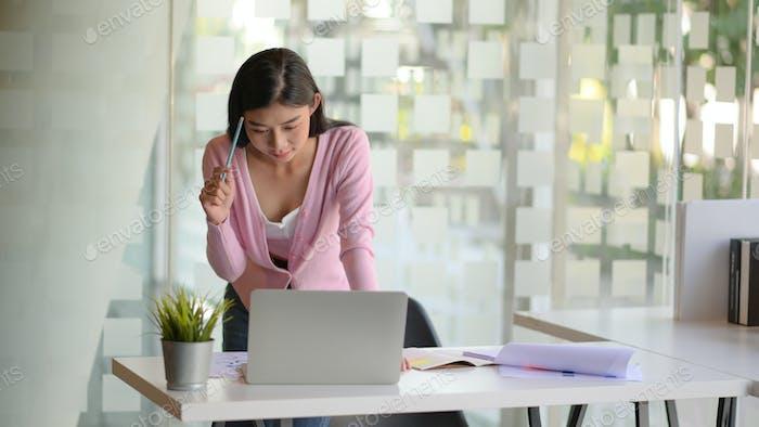 Junge Unternehmerinnen konzentrieren sich auf die Arbeit eines Laptops auf einem weißen Schreibtisch in einem modernen Büro.