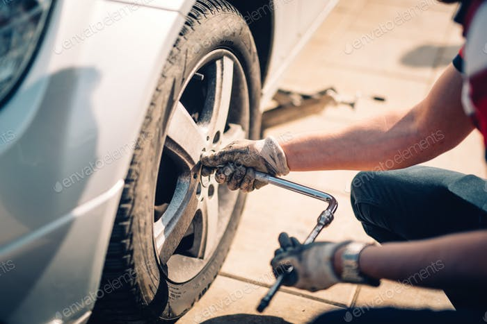 Tire maintenance, damaged car tyre or changing seasonal tires using wrench