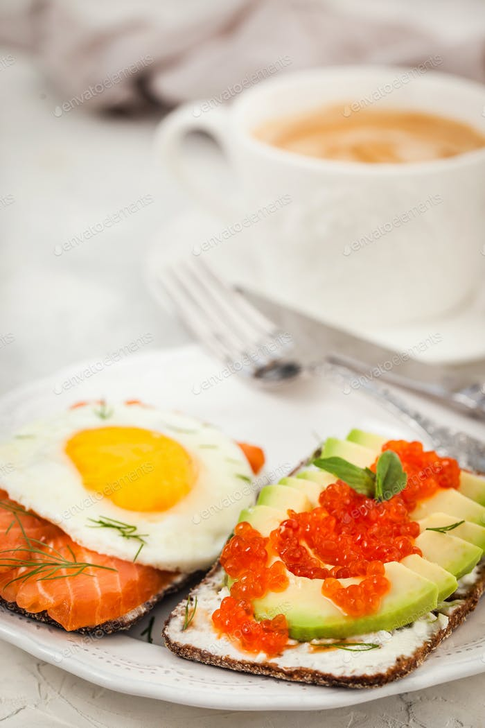 Avocado and red caviar, smoked salmon and fried egg rye toasts f