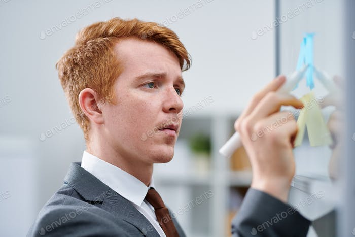Young confident business or financial expert pointing at note on board