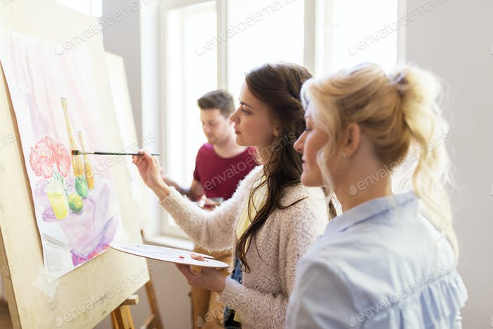 artists with palette and easel at art school