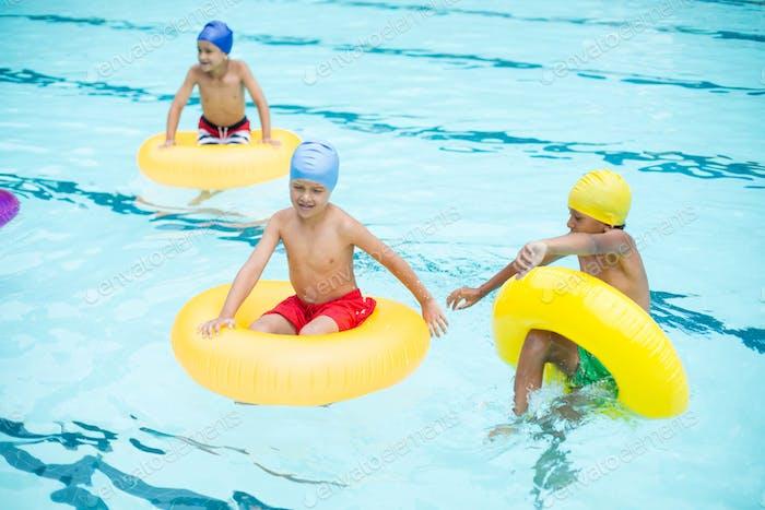 Shirtless boys swimming in pool