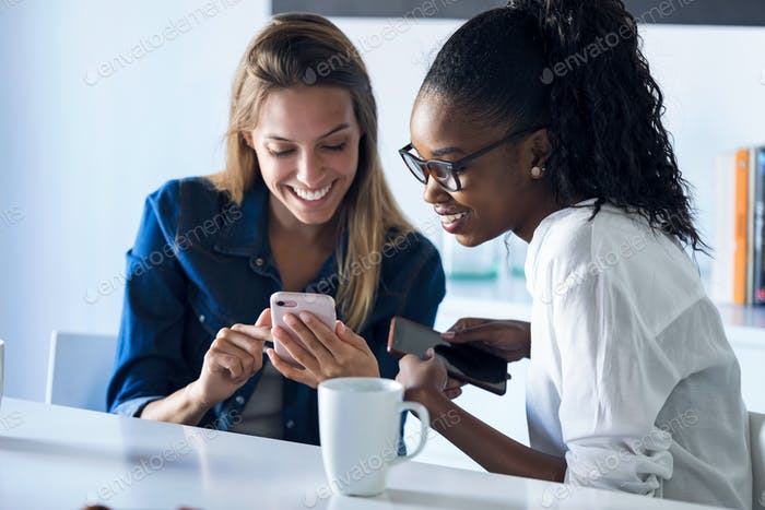 Two pretty young business women using her mobile phone together while taking a break in the office.