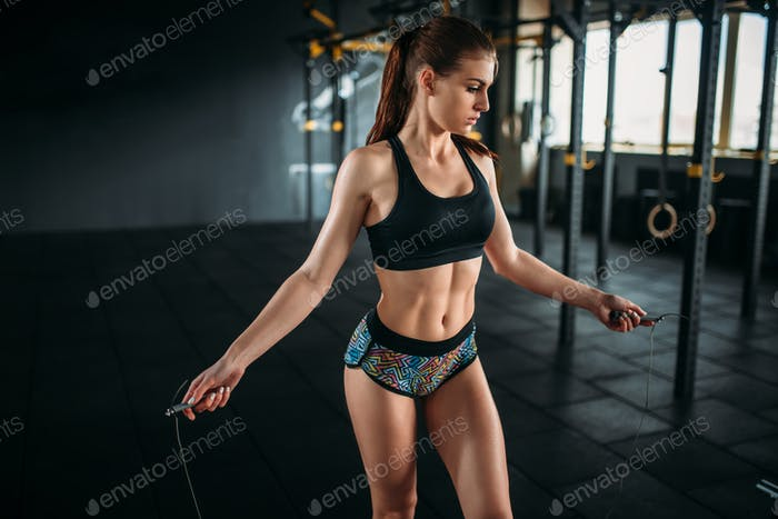 Female athlete exercise with a jump rope in gym