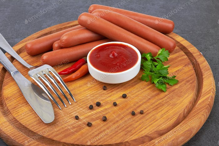 Raw frankfurter sausages with ketchup on cutting board