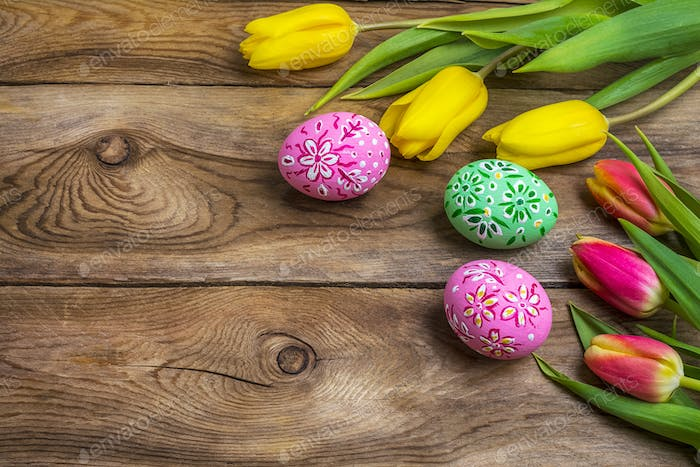 Easter greeting with eggs and yellow red tulips