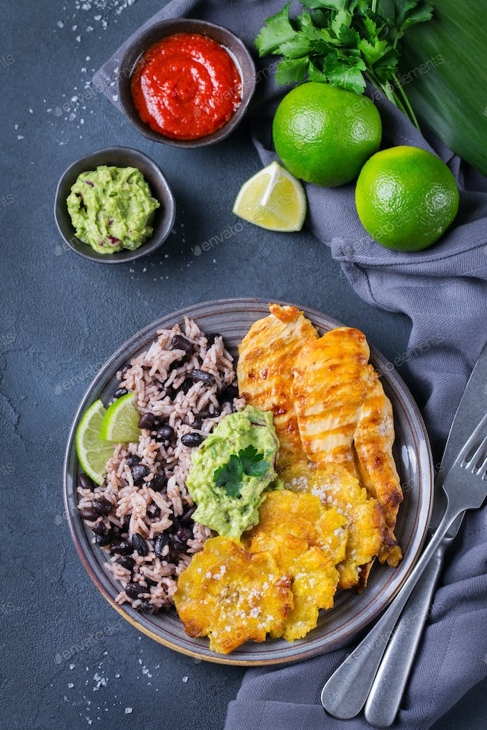 Rice with black beans, fried chicken breast and tostones, plantains