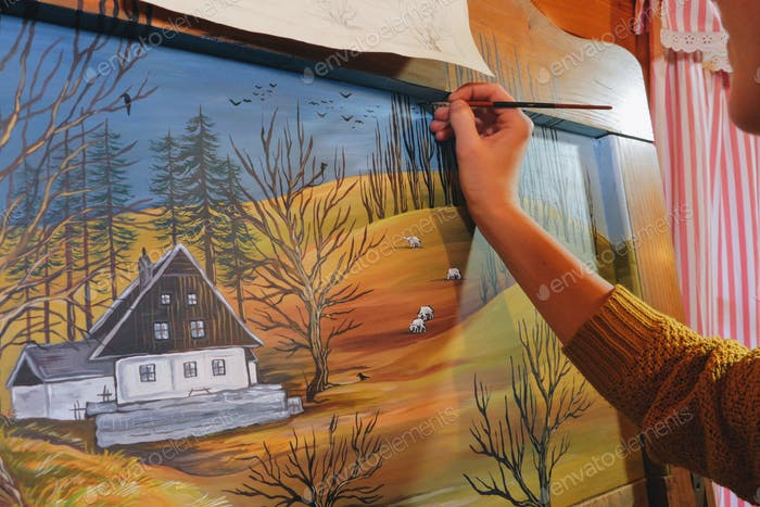 female artist painting a landscape picture on a reclaimed wooden board-art is property released