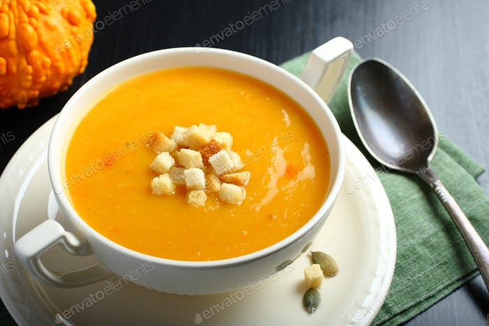 Bowl of pumpkin soup with bread crouton