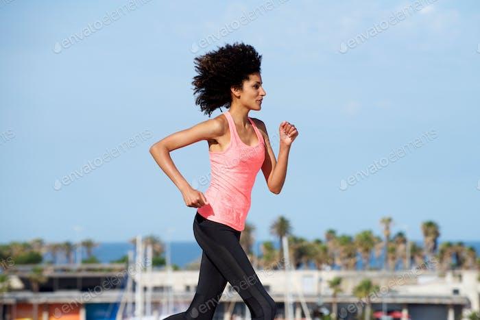 Full length female runner training outside