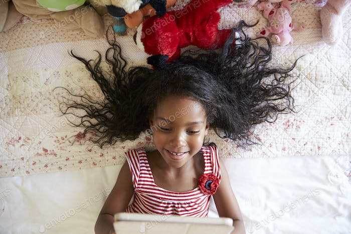 Young Girl Lying On Bed Using Digital Tablet
