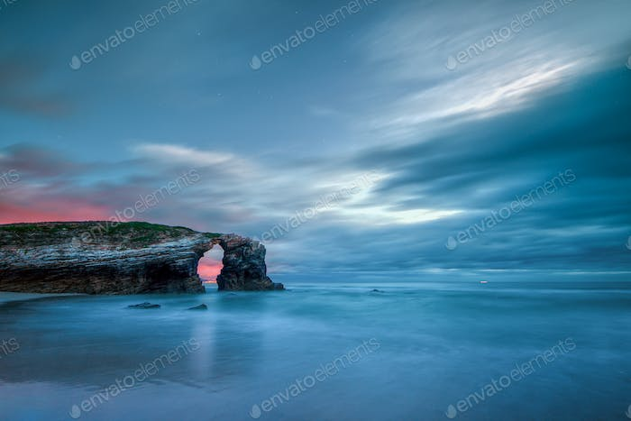 Long exposure of the sunset over the famous stone arch of As Catedrais beach