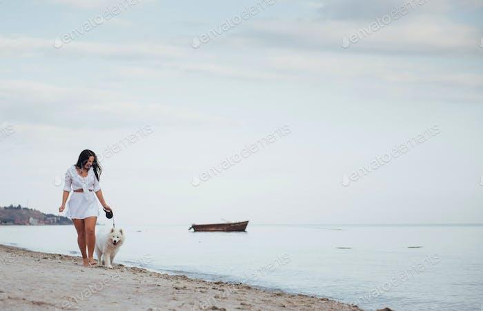 Junge schöne Frau zu Fuß mit ihrem Hund am Strand