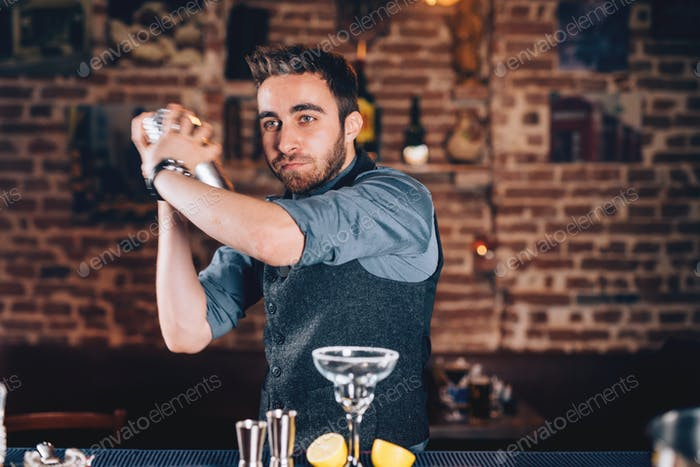 Lifestyle details with barman portrait using shaker and preparing cocktail at bar