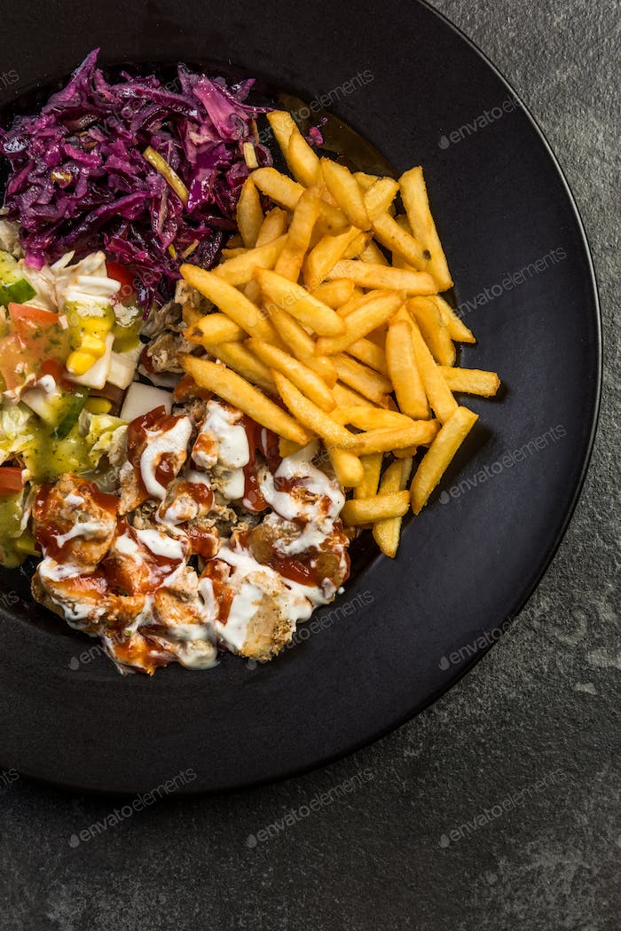 Turkish donner kebab with fries and salad on plate