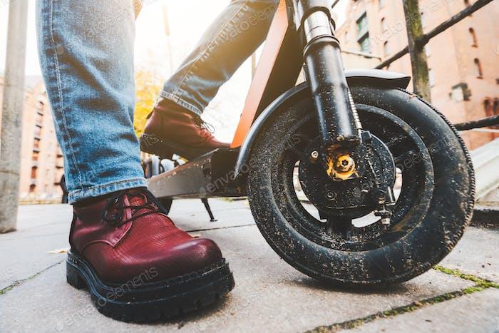 Nahaufnahme von Elektroroller oder E-Scooter und Damenstiefel auf Bürgersteig - E-Mobility oder Micro