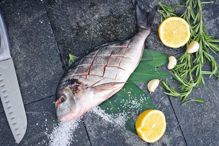 the process of making fresh raw fish dorado on a kitchen cutting board