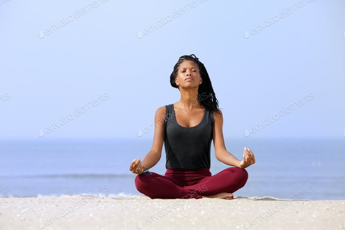 Woman sitting in yoga pose at the beach