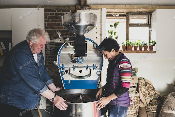 Man and woman standing next to coffee roaster, checking coffee beans.