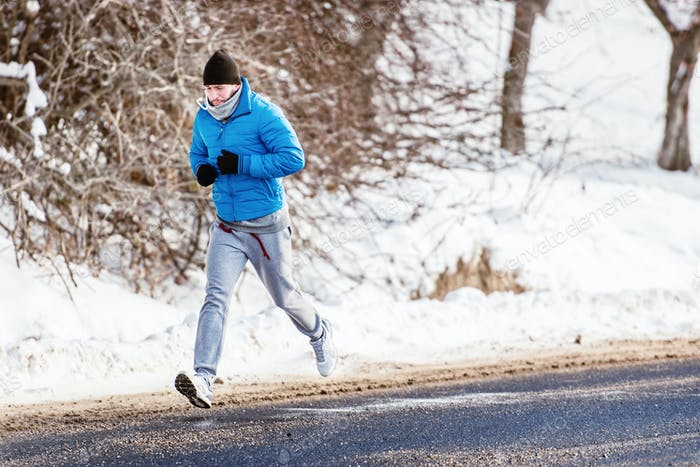 Male athlete working out on snow, running and fitness training