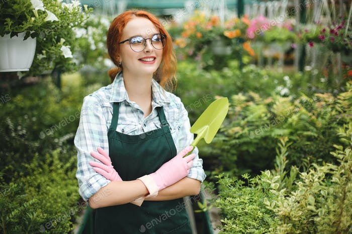 Cheerful florist in apron and pink gloves standing with little garden shovel in hand